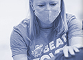 A female health care worker wearing a Beat Covid t-shirt with Gator colors administers a COVID vaccine.