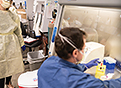 A white male and female researcher work in a lab. The woman is wearing a protective gown and mask. The man is working with samples at a table and is wearing protective gloves and a mask.
