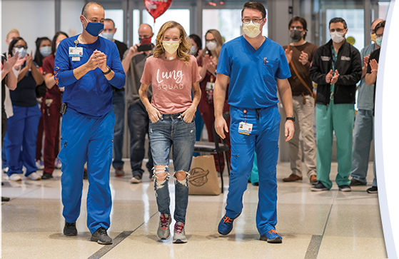 Jill Holker, flanked by two members of her care team wearing blue scrubs, walks through the hospital lobby, surrounded by masked people clapping and holding balloons.