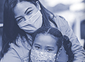 A woman hugs her child and smiles as she steps out of her car. Both are wearing masks.