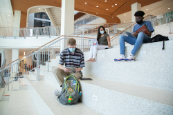 Three people sit on white stairs reading books.