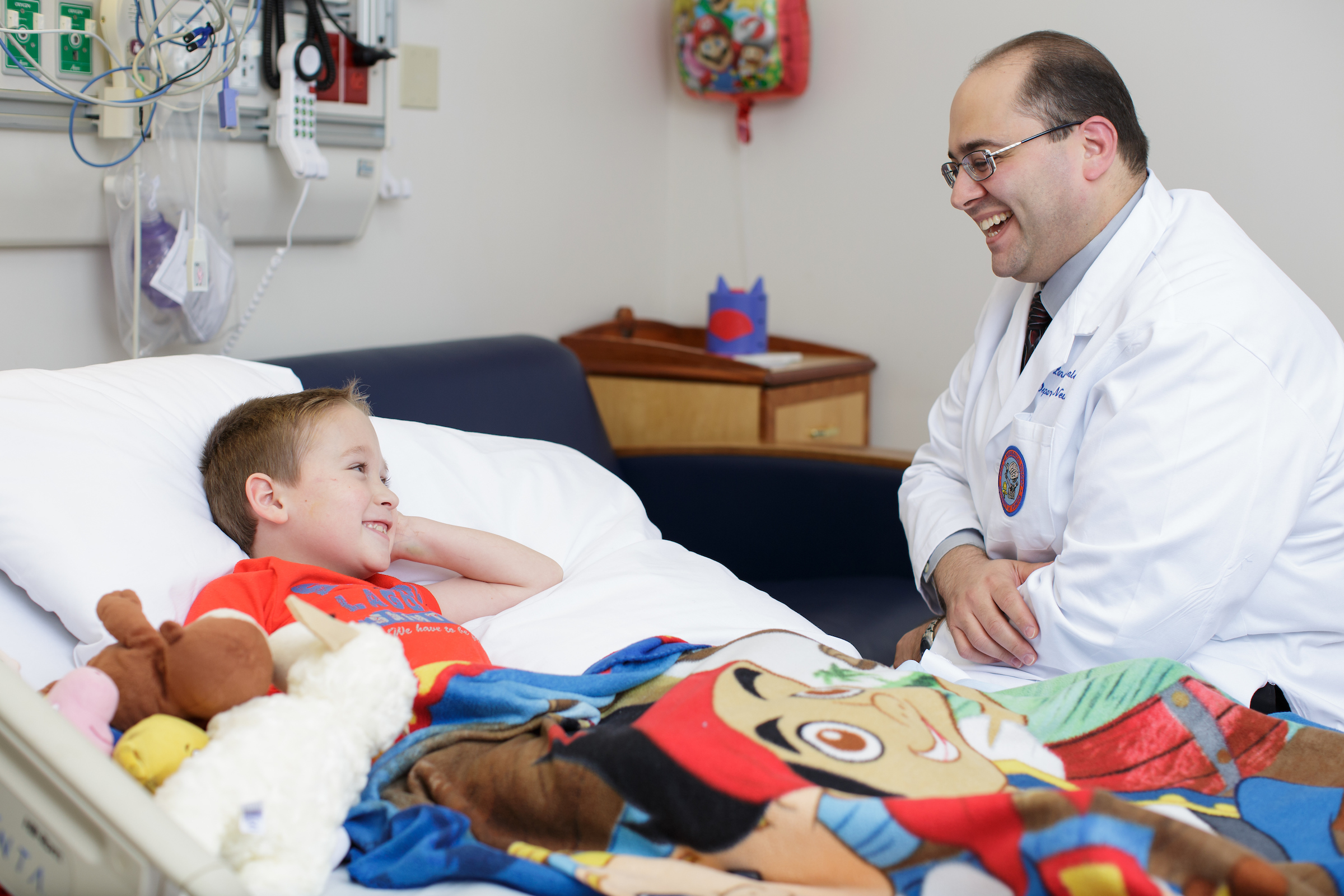 UF Health Children's Hospital neurosurgeon laughs with a young male patient who is lying down in a hospital bed.