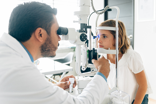 A male ophthalmologist uses a magnifying device to peer into a young female patients eyes.