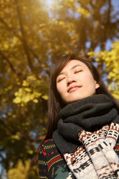A woman takes a few deep breaths while standing in dappled sunlight