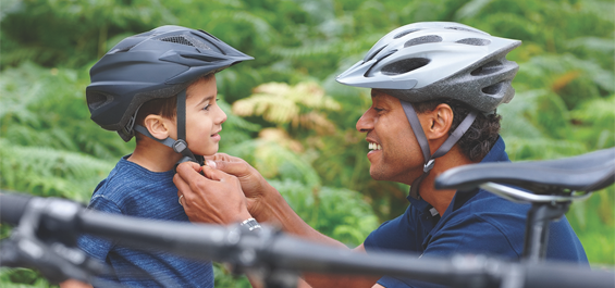 Man helps boy put on bicycle helmet