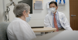two people in white coats talk. Both are wearing masks.