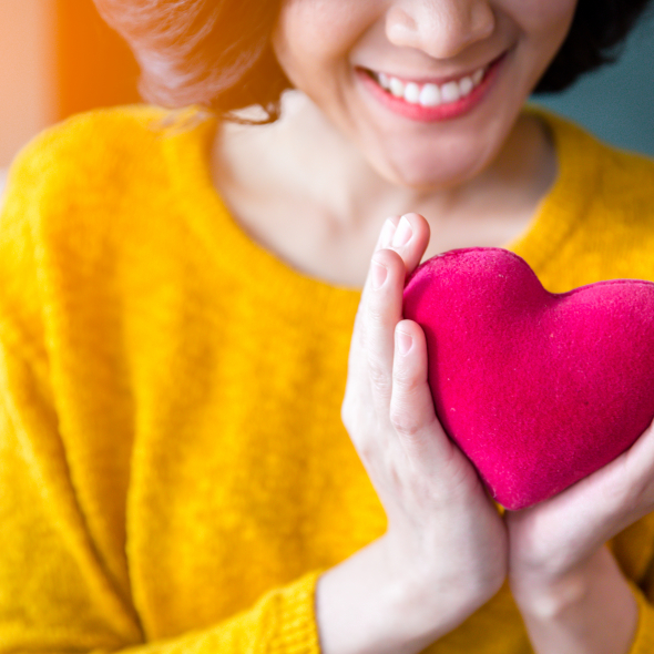 Smiling woman holds plush heart