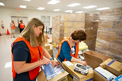 Susan Wigglesworth, R.N., and Shirley Alltop, R.N., CWOCN, sort PPE supplies donated by researchers from UF's McKnight Brain Institute.  Photo by Aimee Bonamie