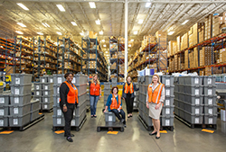 The UF Health Integrated Service Center leadership team provides a view into their distribution center where medical supplies are stocked for delivery to numerous clinical UF Health departments. Left to right: Erica Miller, purchasing manager; Susan Wigglesworth, R.N., strategic sourcing manager; Shirley Alltop, R.N., CWOCN, strategic sourcing manager; Abby Andring, MHA, ISC operations manager; Dawn Watkins, MBA, CMRP, strategic sourcing director.  Photo by Aimee Bonamie