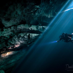 Underwater cave diver entering a cave