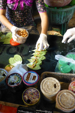 Vendors at the Thri Mingalar Market in Yangon, Myanmar prepare betel quids on Jan. 22, 2018. A betel quid is created by wrapping areca nut, which is the fruit of an areca palm, and slaked lime in a betel vine leaf. Tobacco is often added to the mixture. (Photo courtesy of Roger Papke, Ph.D.)