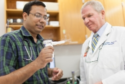 Dr. Mondal (l) and Hendeles demonstrate an Asthmanefrin atomizer, the device that turns the liquid racemic epinephrine into a mist that is inhaled by asthma patient. You can see the mist to the right of the mouthpiece.