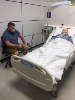 Travis Johnson, a simulation engineer with UF Health's Center for Safety, Simulation and Advanced Learning Technologies, demonstrates the oxygen-pinching technique on the Human Patient Simulator.