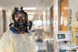 Nila Radhajkrishnan, M.D., chief of the UF College of Medicine's division of hospital medicine, stands in full protective equipment in Unit 75. (Photo by Jesse S. Jones.)