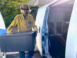 ElderCare of Alachua County volunteer Frank Turner, 88, loads meals for his Meals on Wheels route.
