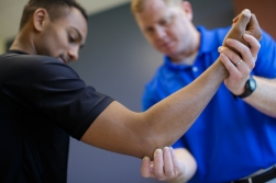 Jason Zaremski, M.D., CAQSM, assistant professor in the UF department of orthopedics and rehabilitation, examines a patient's elbow during an office visit.