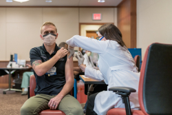 """I think it's a step toward getting back to some kind of normal,'' said Samuel J. Overly, B.S.N., R.N.-B.C., a trauma nurse and clinical leader in the UF Health adult emergency department, after receiving the inaugural vaccination.  Credit: Louis Brems"