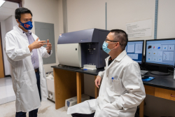 Dr. Liang Zhou speaks to his postdoctoral associate, Dr. Lifeng Xiong, in his laboratory. Xiong was first author on a recent paper published by the Zhou laboratory in Science Immunology relating to the protein Ahr.