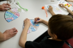 "A boy colors a ""brain hat,"" which was used during an event to teach young students about the regions of the brain. The students visited the Evelyn F. and William L. McKnight Brain Institute of the University of Florida for a Brain Awareness Week event."