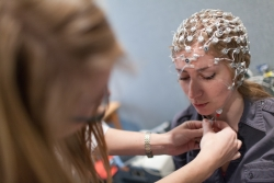A participant gets fitted with an electrode net that monitors brain activity.