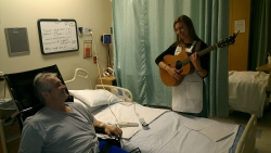 James Geisler, a hip replacement patient at UF Health Shands Rehab Hospital, listens contently as Kelseanne Breder plays guitar and sings for him as part of her job as an artist in residence with the Arts in Medicine Program.