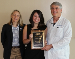 From left to right are Dr. Dana Zimmel, associate dean for clinical services at the UF College of Veterinary Medicine, Dr. Mandy Wallace, holding her award and Dr. Dan Lewis, a professor of small animal surgery. Wallace received the American Association of Veterinary Clinicians' 2016 Resident Award and was recognized during a recent meeting of the UF Veterinary Hospitals. (Photo courtesy of Dr. Mandy Wallace)