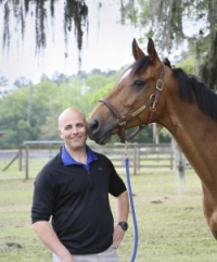 Dr. Andrew Smith, a UF large animal surgery resident, is shown with a horse helped to treat. (Photo by Diana Andersen-Davis Photography)