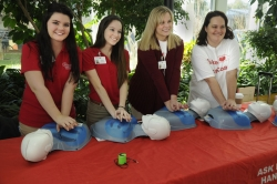 Take Heart First Coast volunteers demonstrate hands-only CRP during the UF Health Jacksonville Wellness Fair.