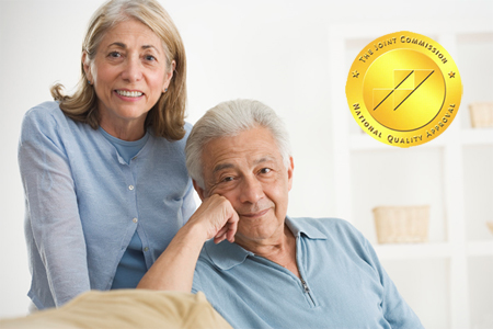 Couple smiling with joint commission seal.