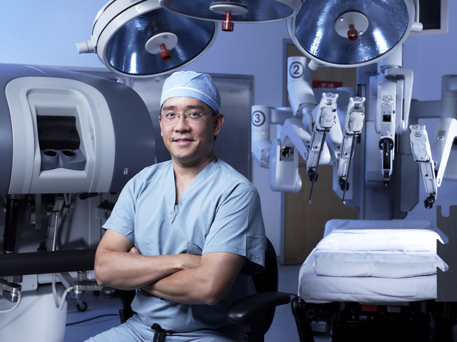 Dr. Su in front of robotic surgery equipment
