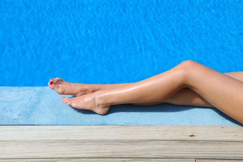 Legs tanning by pool