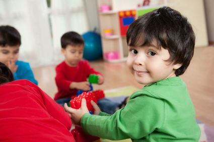 little boy playing with friends in a playroom