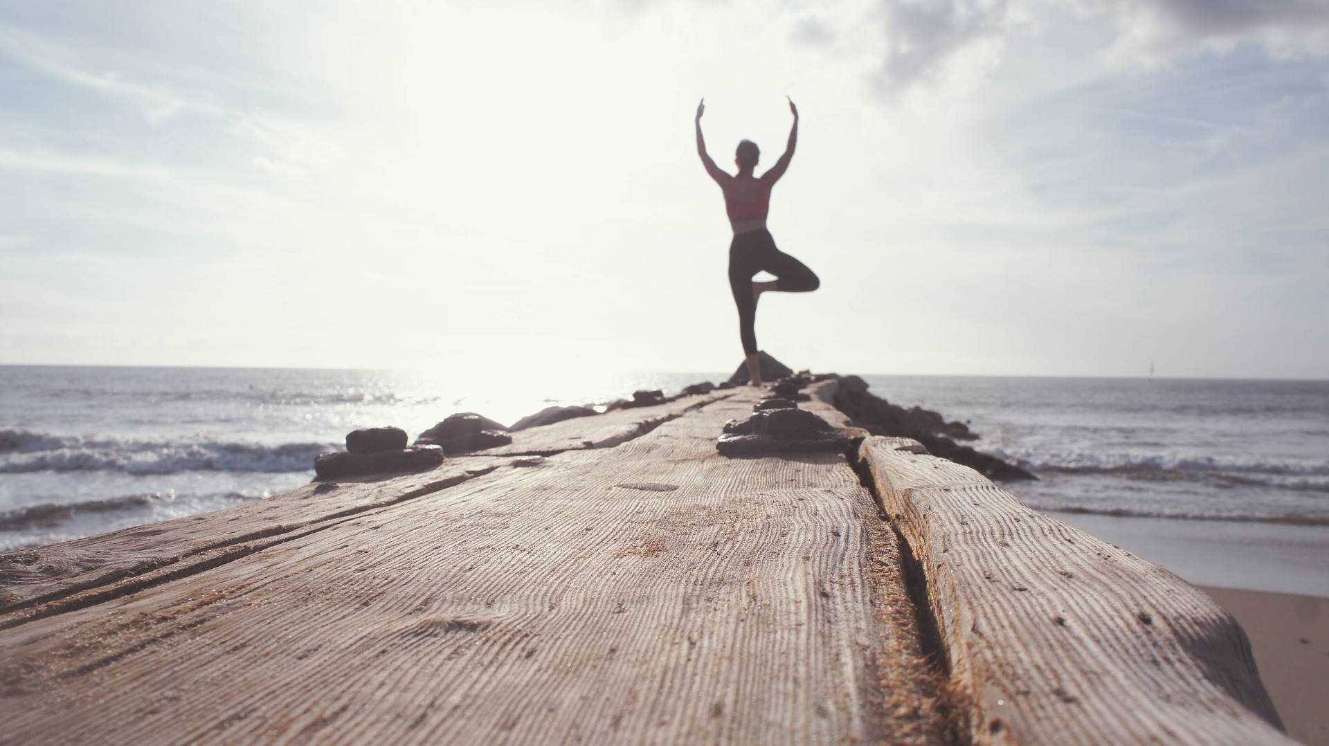Woman doing yoga on a rocky pier.