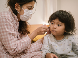 A woman wearing a white mask and wearing a plaid shirt uses a thermometer in the ear of a small child