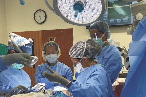 Maryam Rahman, MD, MS, right, and Si Chen, MD, middle, operate on an encephalocele patient.