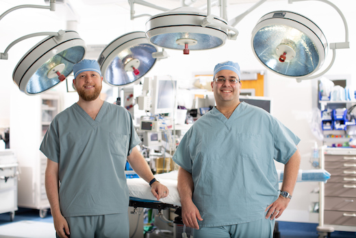 Two pediatric neurosurgeons stand proudly in an operating room environment