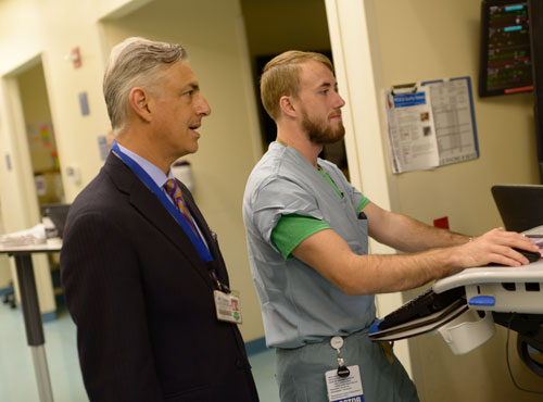 Mark Bleiweis, MD, director of the UF Health Congenital Heart Center and chief of congenital cardiothoracic surgery at UF Health, works with a team member in the pediatric cardiac intensive care unit.