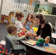woman playing in a playroom with a group of children