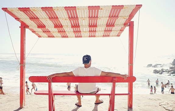 Elderly man under the shade at the beach