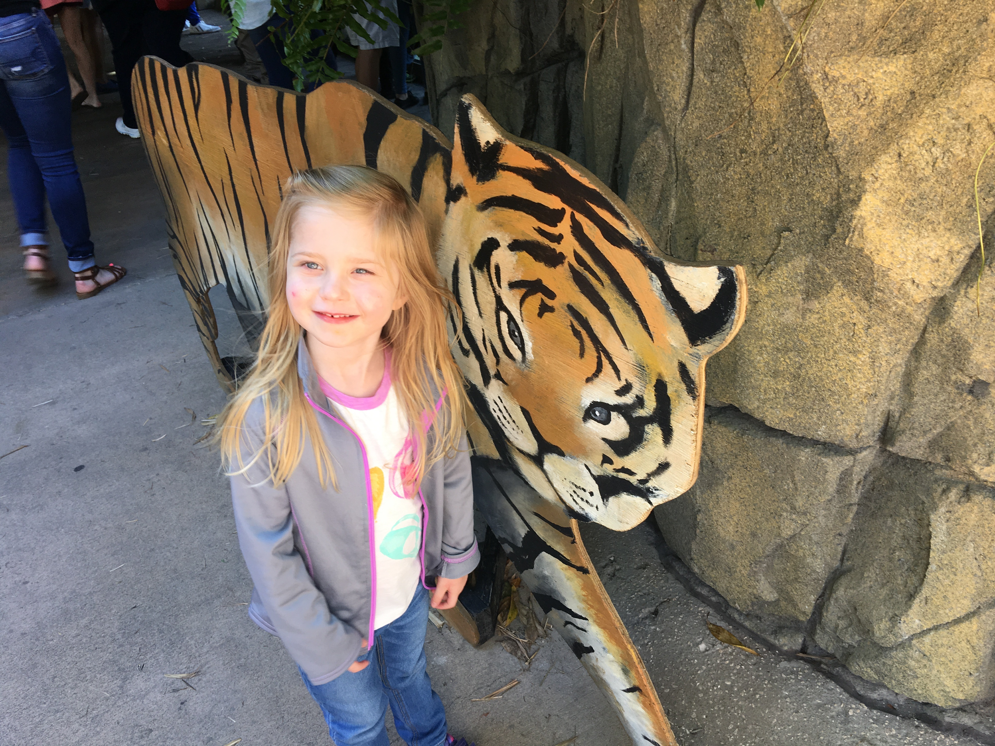 A young girl stands next to a painted wooden tiger.