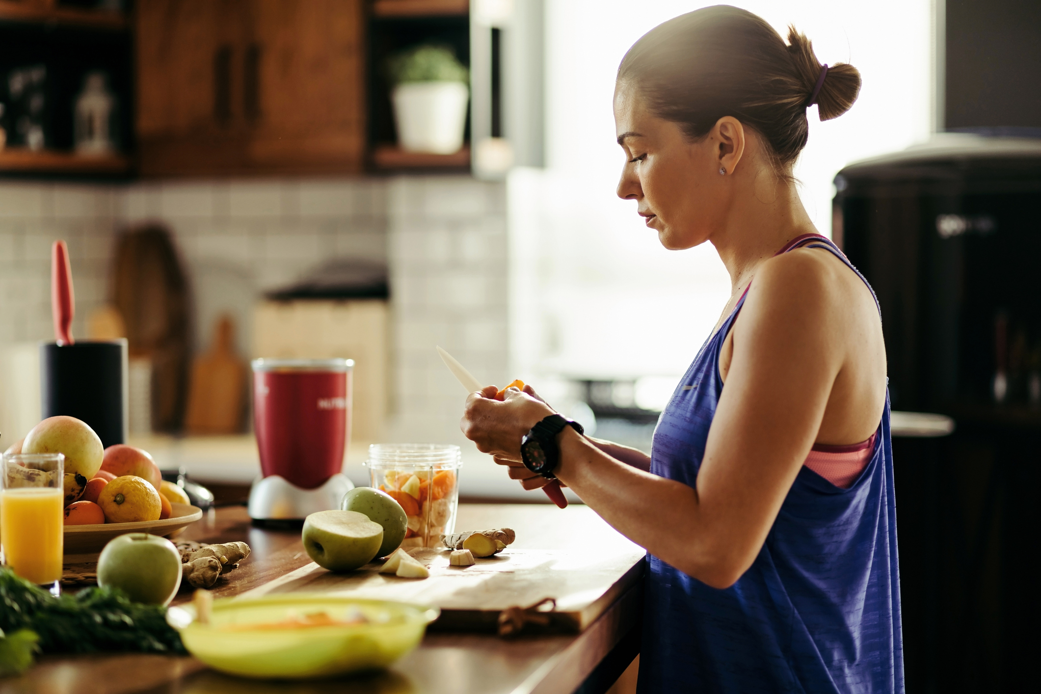 woman in athletic clothing standing at a kitchen counter cutting up fresh fruit for a smoothie