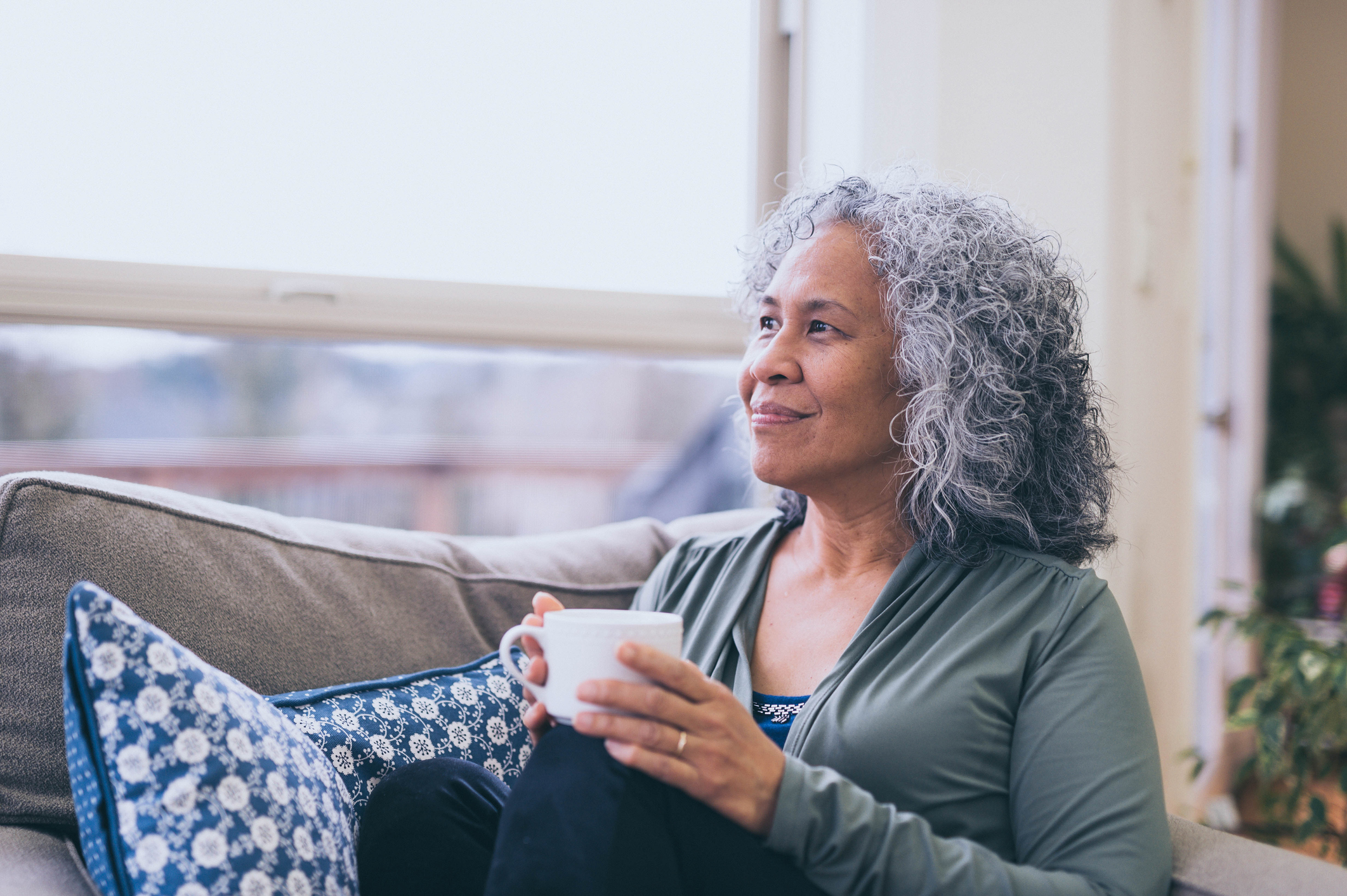 Hawiian woman sitting on the couch holding a cup of coffee and looking into the distance