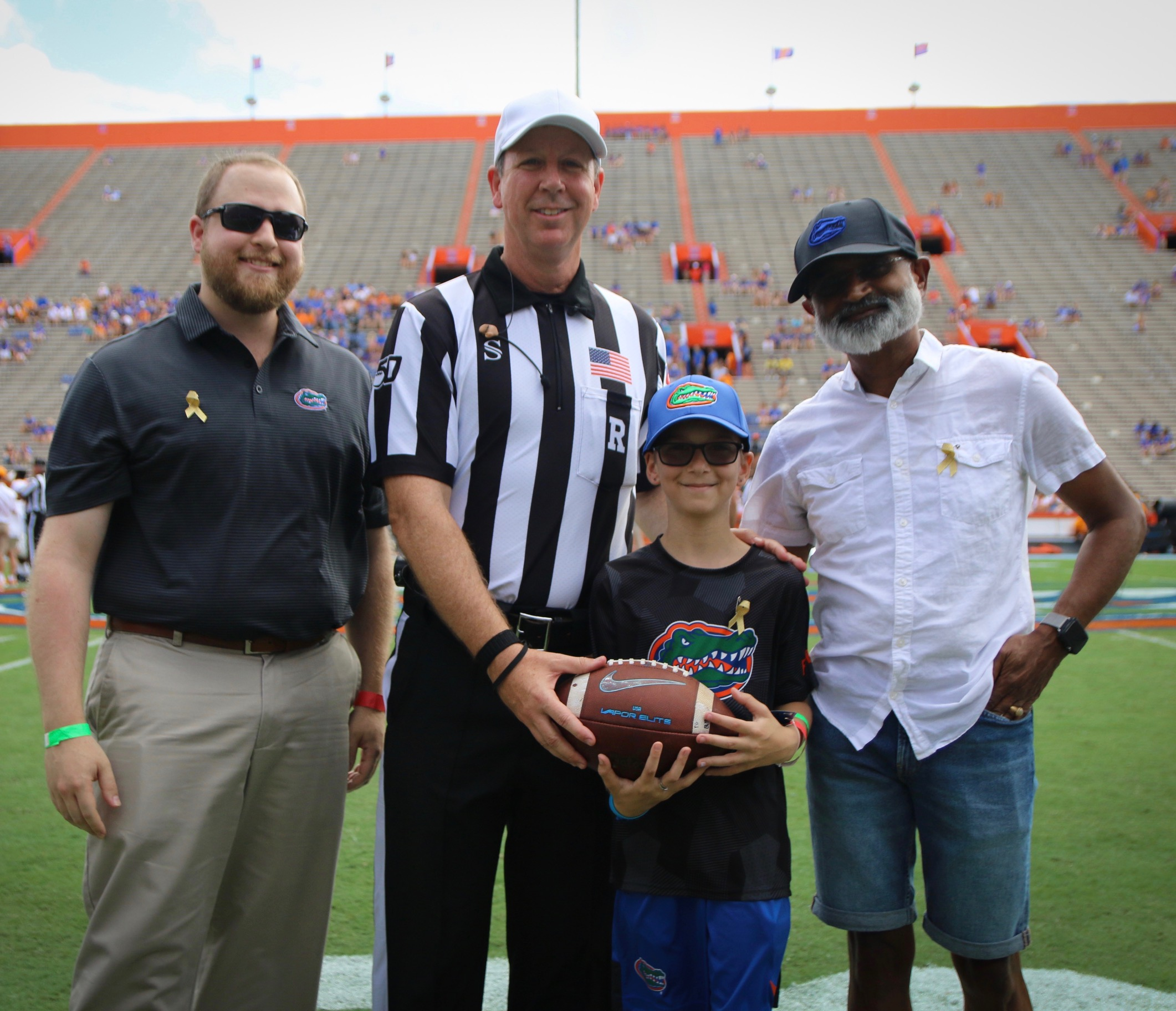 Mikah with the game ball, his doctor and a referee in The Swamp