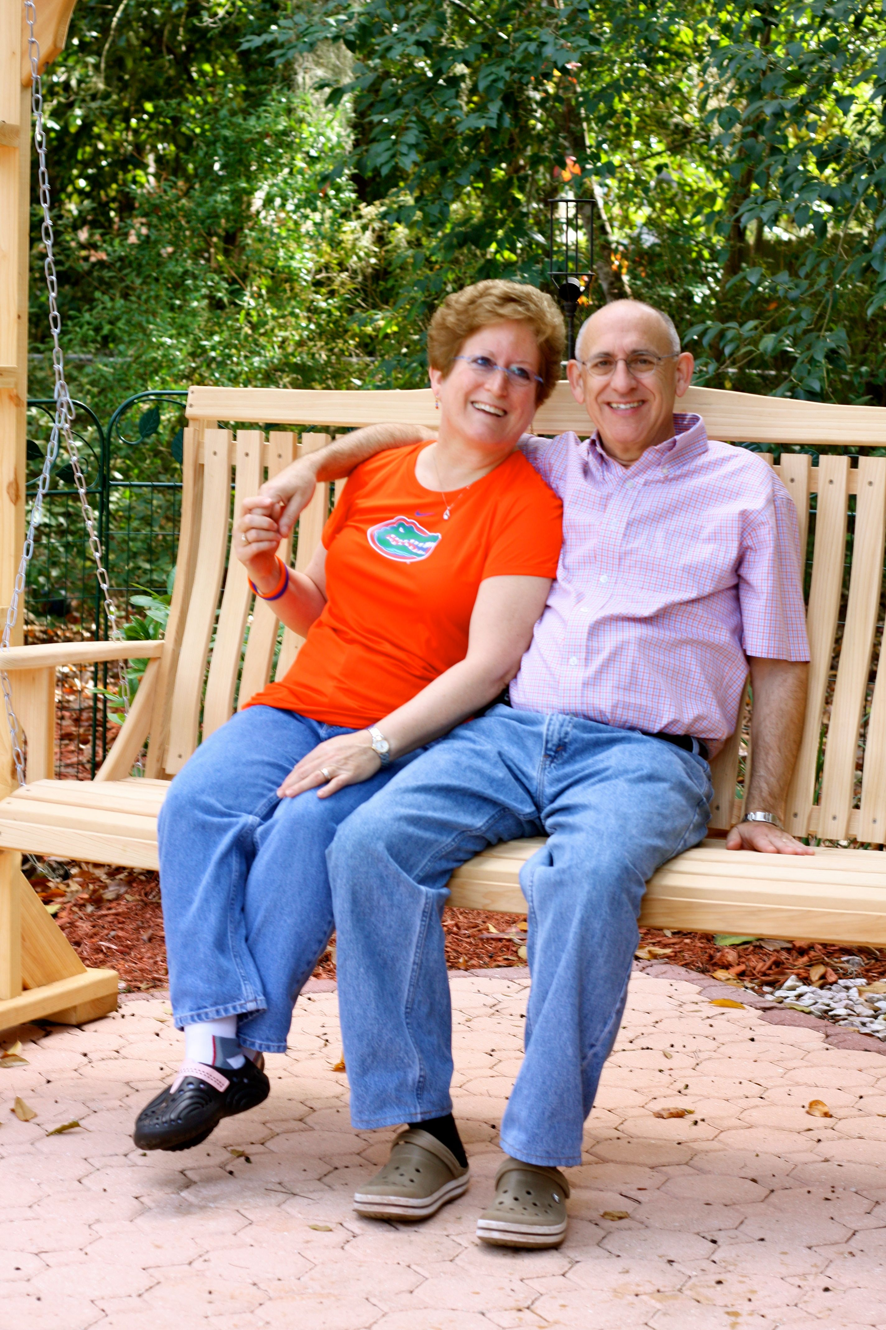 Bob Cohen & his wife sitting on a swing.