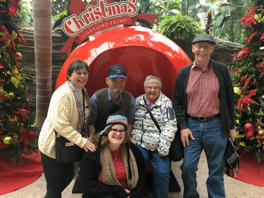 A group of five people posing with a large Christmas ornament that says Christmas at Gaylord Palms