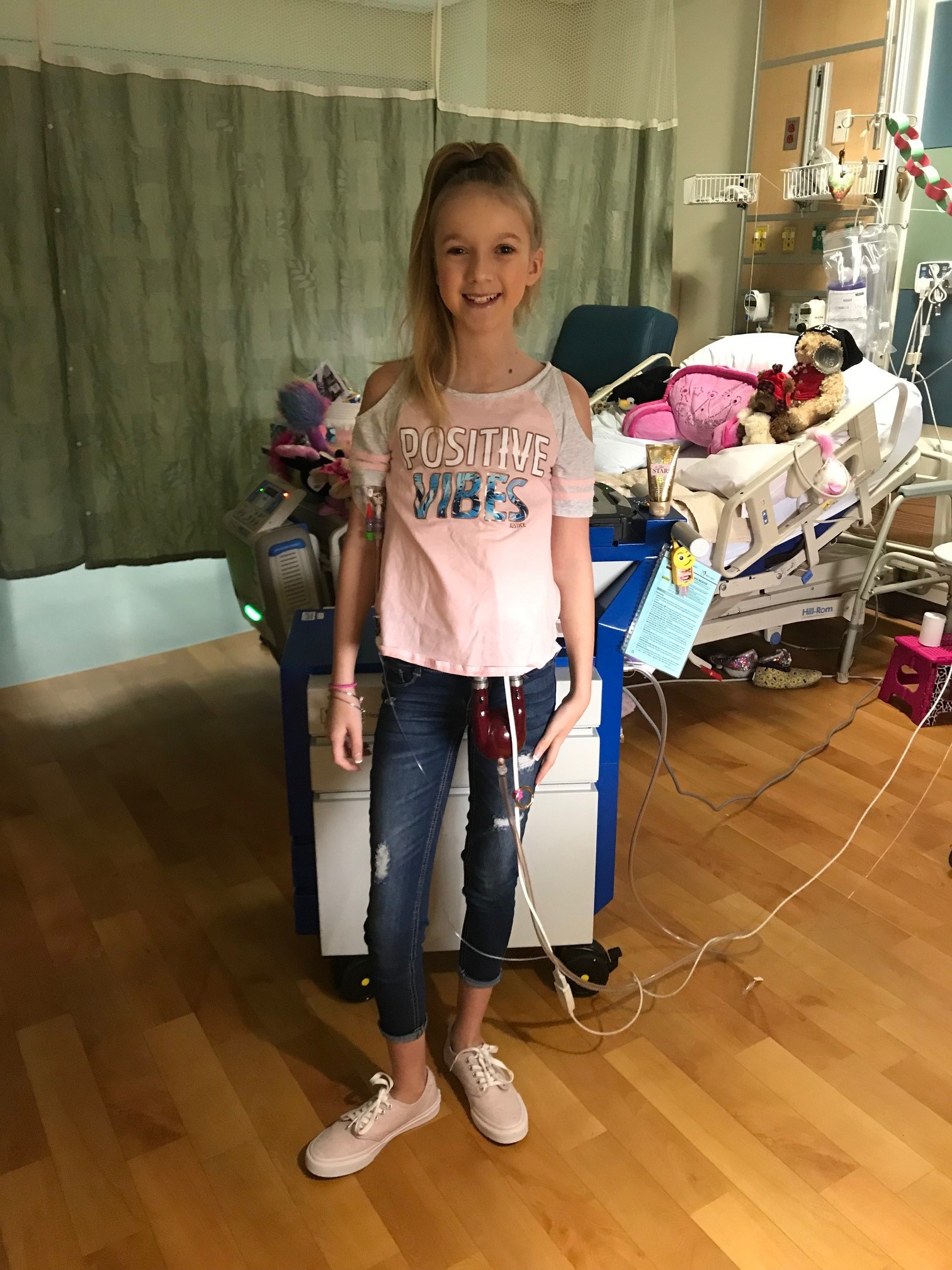 a teen girl posing in a hospital room wearing every day clothes