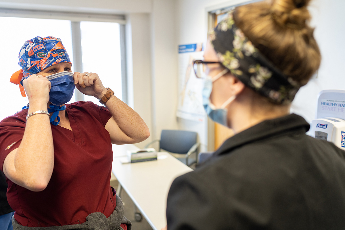 Two women health care providers talk while wearing masks.