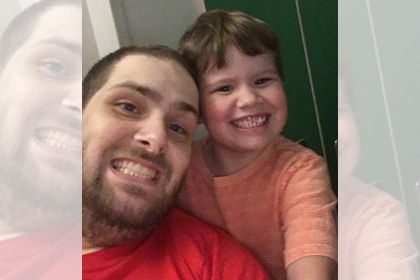 Bobby and a child in a selfie. Both are smiling at the camera.