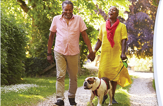 An older Black couple walks down a gravel road surrounded by trees in bright sunlight. They are walking a bulldog and laughing.