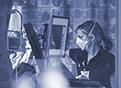 A nurse in the COVID-19 unit can be seen through a window as she checks several health monitors.